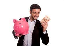 Hombre de negocios que sostiene la hucha rosada con el dinero disponible Foto de archivo libre de regalías