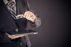 Hombre de negocios que sostiene la lupa y la tableta imagen de archivo libre de regalías