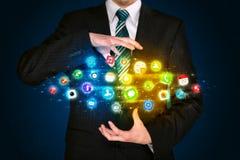 Hombre de negocios que sostiene la nube del icono del app Imagenes de archivo