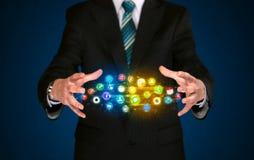 Hombre de negocios que sostiene la nube del icono del app Imagen de archivo