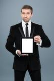 Hombre de negocios que sostiene la PC digital de la tableta con la pantalla en blanco Imágenes de archivo libres de regalías