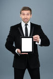 Hombre de negocios que sostiene la PC digital de la tableta con la pantalla en blanco Foto de archivo libre de regalías
