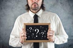 Hombre de negocios que sostiene la pizarra con los signos de interrogación Fotos de archivo libres de regalías