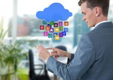 Hombre de negocios que sostiene la tableta de cristal con los iconos de los apps en oficina brillante Fotografía de archivo libre de regalías