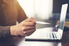 Hombre de negocios que sostiene la tarjeta de visita blanca en la oficina vendimia Imagen de archivo