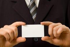 Hombre de negocios que sostiene la tarjeta de visita en blanco Fotos de archivo libres de regalías
