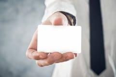 Hombre de negocios que sostiene la tarjeta de visita en blanco con las esquinas redondeadas Fotos de archivo libres de regalías