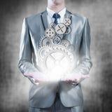 Hombre de negocios que sostiene los engranajes en las palmas, concepto de la estrategia empresarial Foto de archivo libre de regalías
