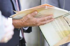 Hombre de negocios que sostiene los papeles Foto de archivo