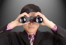 Hombre de negocios que sostiene los prismáticos f imagenes de archivo