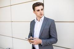 Hombre de negocios que sostiene smartphone móvil usando la chaqueta del traje del mensaje del SMS del app que lleva que manda un  Fotos de archivo libres de regalías