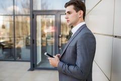 Hombre de negocios que sostiene smartphone móvil usando la chaqueta del traje del mensaje del SMS del app que lleva que manda un  Fotos de archivo
