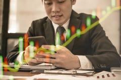 Hombre de negocios que sostiene smartphone y que usa el app Mensaje texting del hombre Foto de archivo