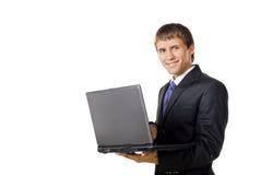 Hombre de negocios que sostiene su computadora portátil Imagen de archivo libre de regalías