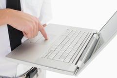 Hombre de negocios que sostiene su ordenador portátil y que usa la almohadilla táctil Foto de archivo libre de regalías