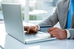 Hombre de negocios que sostiene su tarjeta de crédito para pagar Foto de archivo