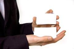 Hombre de negocios que sostiene tarjetas de visita en blanco Imágenes de archivo libres de regalías