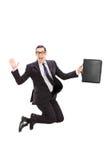 Hombre de negocios que sostiene un caso y que salta en el aire Imágenes de archivo libres de regalías