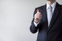 Hombre de negocios que sostiene un dardo Foto de archivo libre de regalías