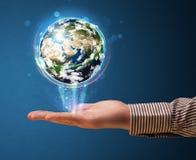 Hombre de negocios que sostiene un globo de la tierra que brilla intensamente Imagen de archivo libre de regalías