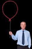 Hombre de negocios que sostiene un globo de la tiza Imagenes de archivo