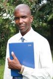 Hombre de negocios que sostiene un libro Imágenes de archivo libres de regalías