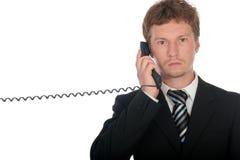 Hombre de negocios que sostiene un microteléfono de teléfono Foto de archivo libre de regalías