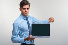 Hombre de negocios que sostiene un ordenador portátil contra un fondo blanco Foto de archivo libre de regalías