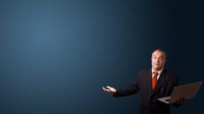 Hombre de negocios que sostiene un ordenador portátil y que presenta el espacio de la copia Imágenes de archivo libres de regalías