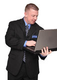 Hombre de negocios que sostiene un ordenador portátil Imágenes de archivo libres de regalías