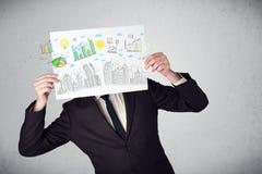 Hombre de negocios que sostiene un papel con las cartas y el paisaje urbano en o delantero Foto de archivo