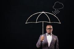 Hombre de negocios que sostiene un paraguas Imagen de archivo libre de regalías