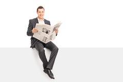 Hombre de negocios que sostiene un periódico asentado en un panel Imagen de archivo