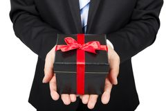 Hombre de negocios que sostiene un regalo Imagen de archivo
