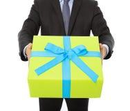 Hombre de negocios que sostiene un regalo Aislado en blanco imágenes de archivo libres de regalías