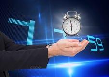Hombre de negocios que sostiene un reloj contra fondo con el reloj Fotografía de archivo libre de regalías