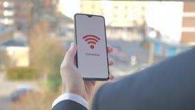Hombre de negocios que sostiene un smartphone que conecta con el wifi almacen de video