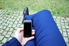 Hombre de negocios que sostiene un teléfono celular y que escribe el mensaje del SMS Foto de archivo libre de regalías