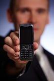 Hombre de negocios que sostiene un teléfono móvil Fotos de archivo libres de regalías