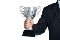 Hombre de negocios que sostiene un trofeo de la plata del campeón en el fondo blanco fotos de archivo libres de regalías