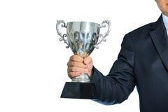 Hombre de negocios que sostiene un trofeo de la plata del campeón en el fondo blanco Imágenes de archivo libres de regalías