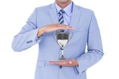 Hombre de negocios que sostiene un trofeo en sus manos contra el fondo blanco imágenes de archivo libres de regalías