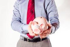 Hombre de negocios que sostiene una batería del cerdo Imágenes de archivo libres de regalías