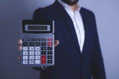Hombre de negocios que sostiene una calculadora imagen de archivo