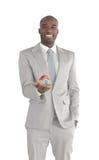 Hombre de negocios que sostiene una casa en sus manos Imagen de archivo