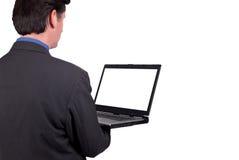 Hombre de negocios que sostiene una computadora portátil imagen de archivo libre de regalías