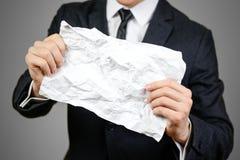 Hombre de negocios que sostiene una hoja arrugada del papel A4 Cierre para arriba Aislador Fotografía de archivo libre de regalías