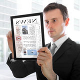 Hombre de negocios que sostiene una PC del touchpad con el e-periódico Fotografía de archivo libre de regalías