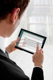Hombre de negocios que sostiene una PC del touchpad, escribiendo el email Foto de archivo libre de regalías