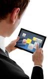 Hombre de negocios que sostiene una PC del touchpad usando los aparatos Fotografía de archivo libre de regalías